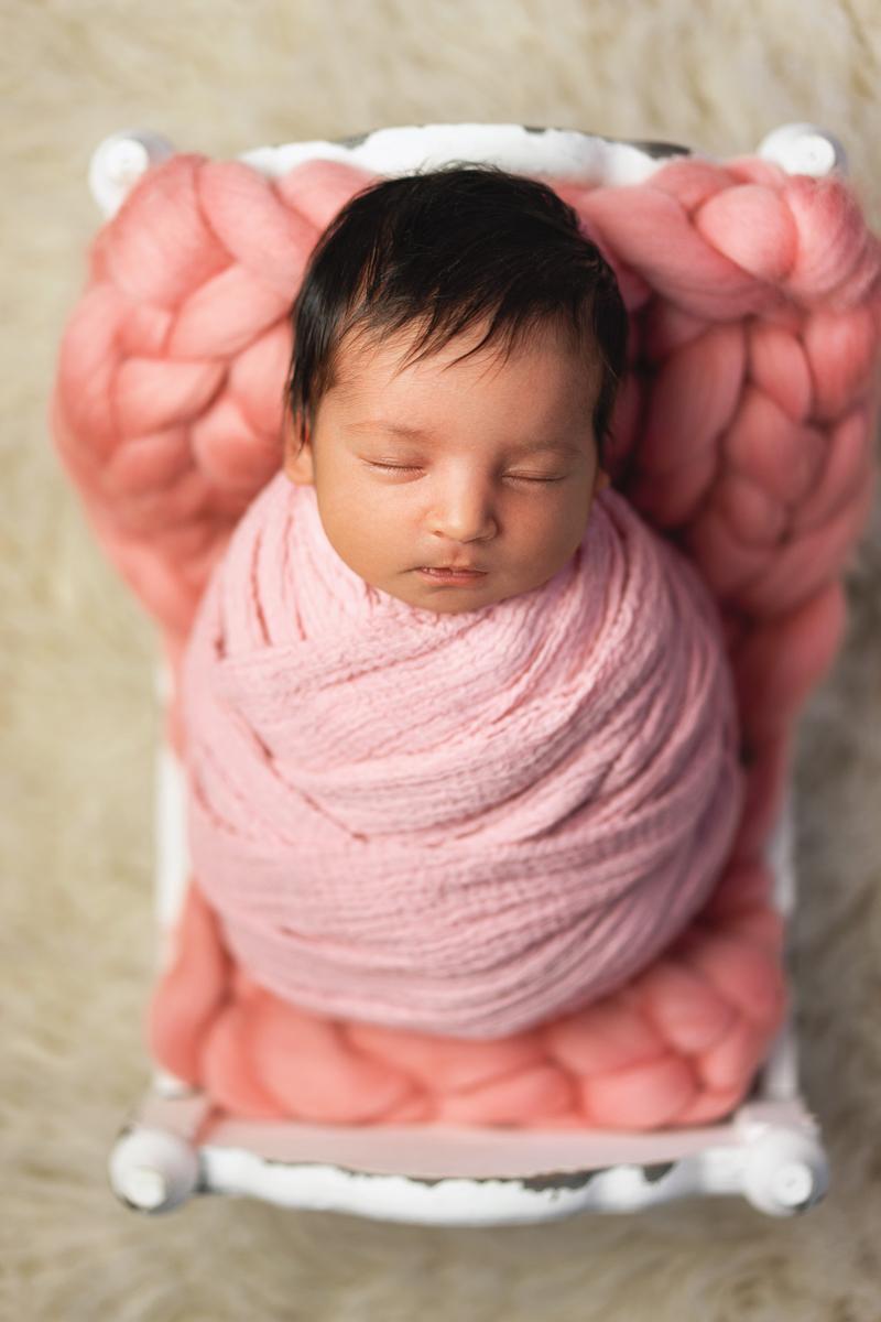 Kleines Baby auf Bettchen Neugeborenenfotos Mädchen in Bremen Babyfotografin OHZ
