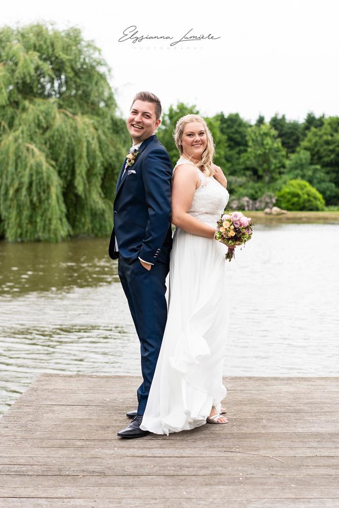 Brautpaarfotos Rücken an Rücken mit Brautstrauß