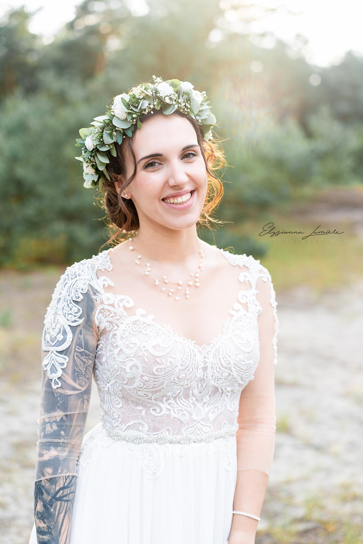 Braut mit Spitzenkleid und Blumenkranz im Sonnenuntergang