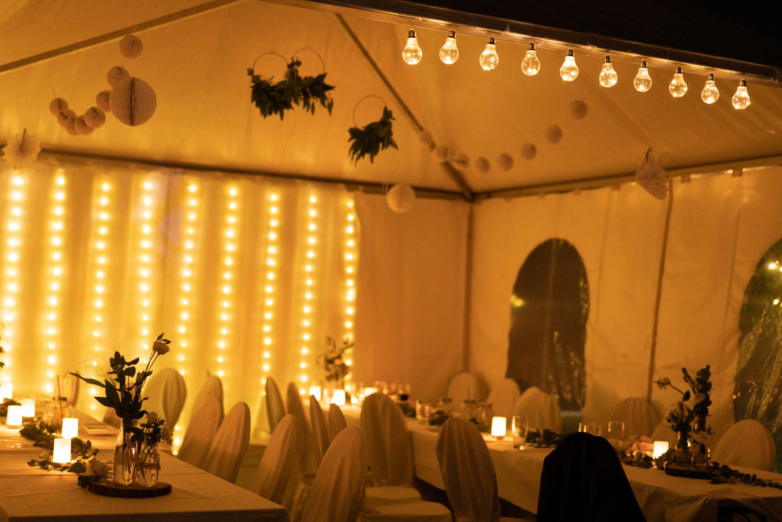 Mit Lichterketten geschmücktes Zelt am Abend auf der Hochzeit