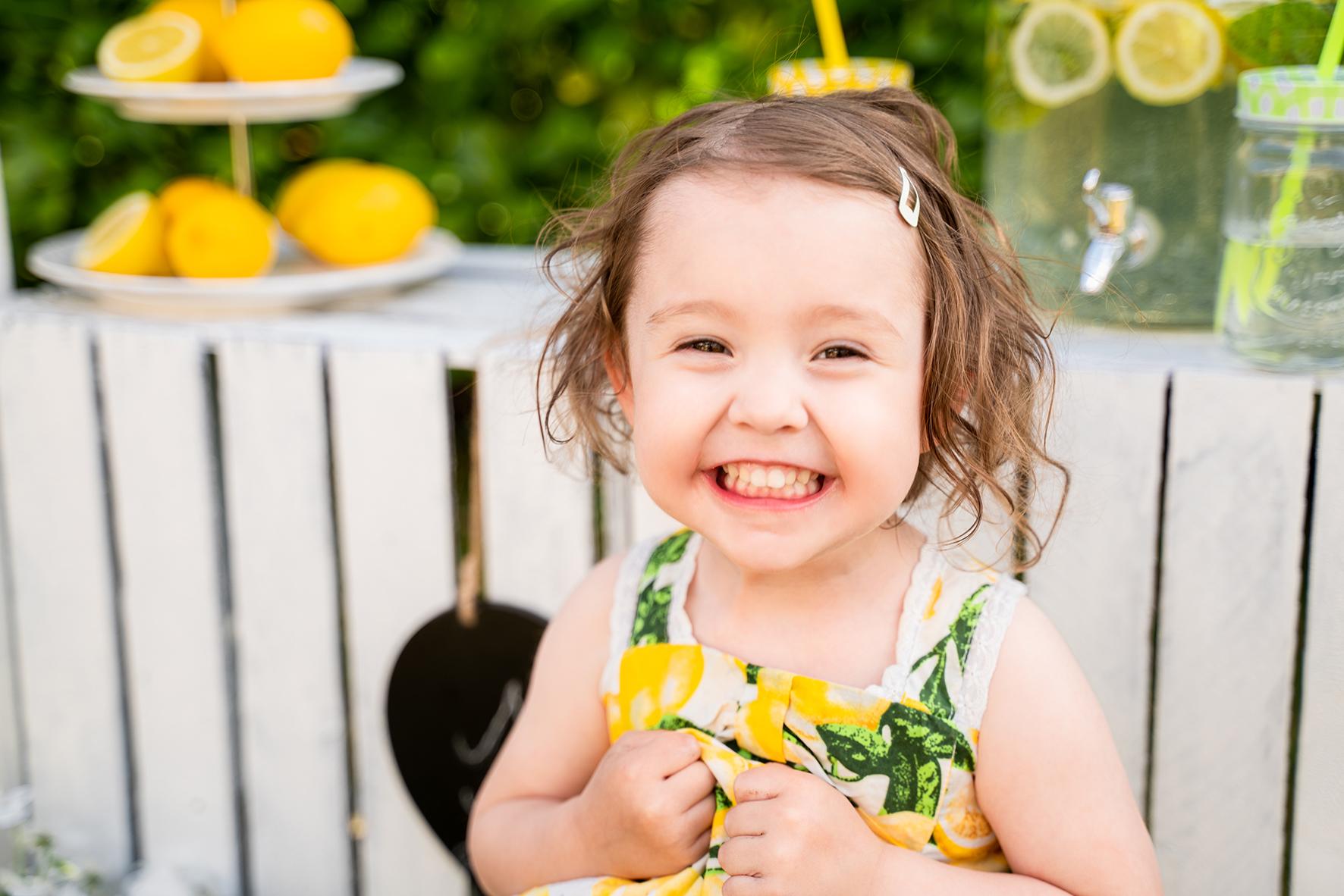 Lachendes Kind beim Fotoshooting mit Zitronen