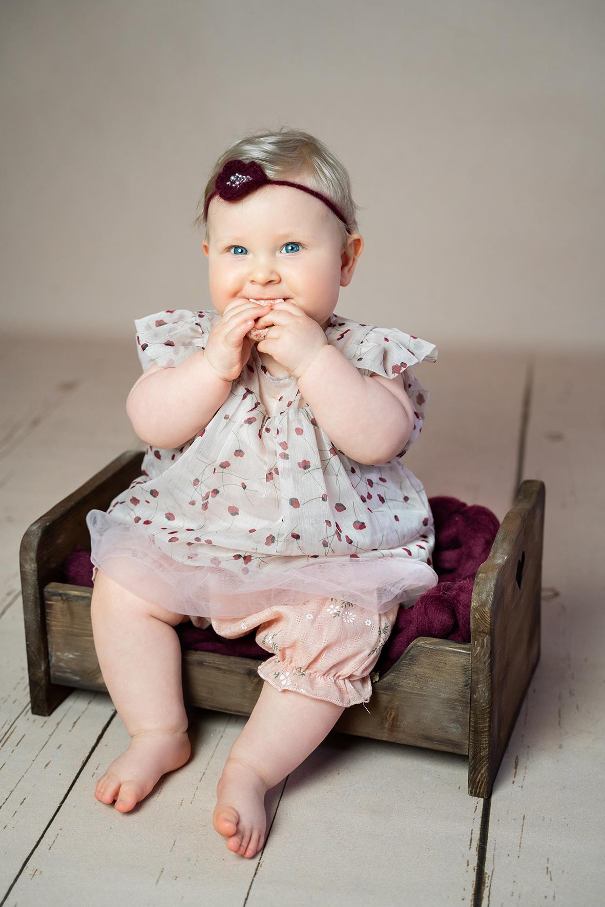 Baby im Sitzalter Fotoshooting mit kleinem Holzbett im Fotostudio Bremen