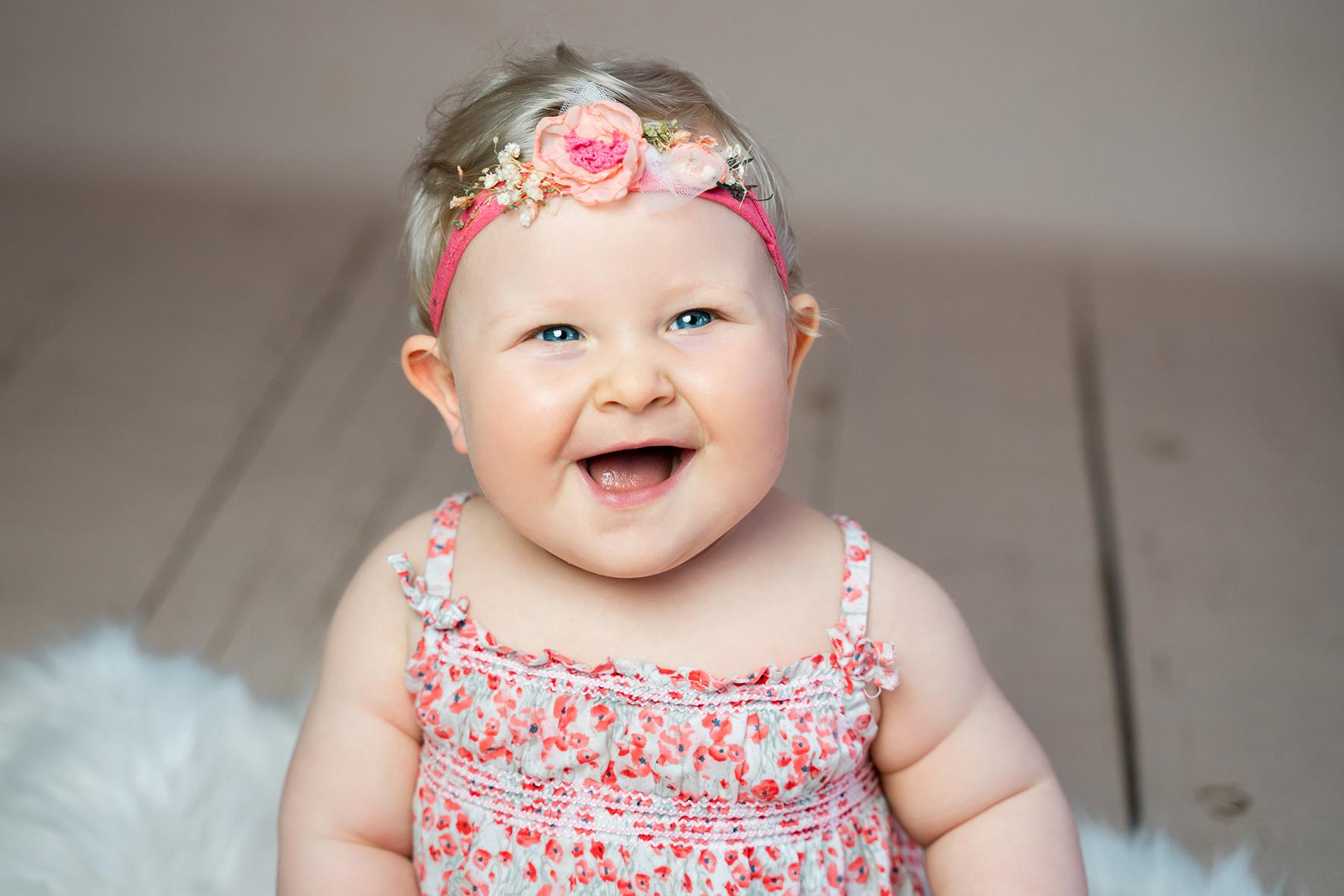 Kinderfotoshooting im Studio Mädchen mit Blumen im Haar lacht herzlich