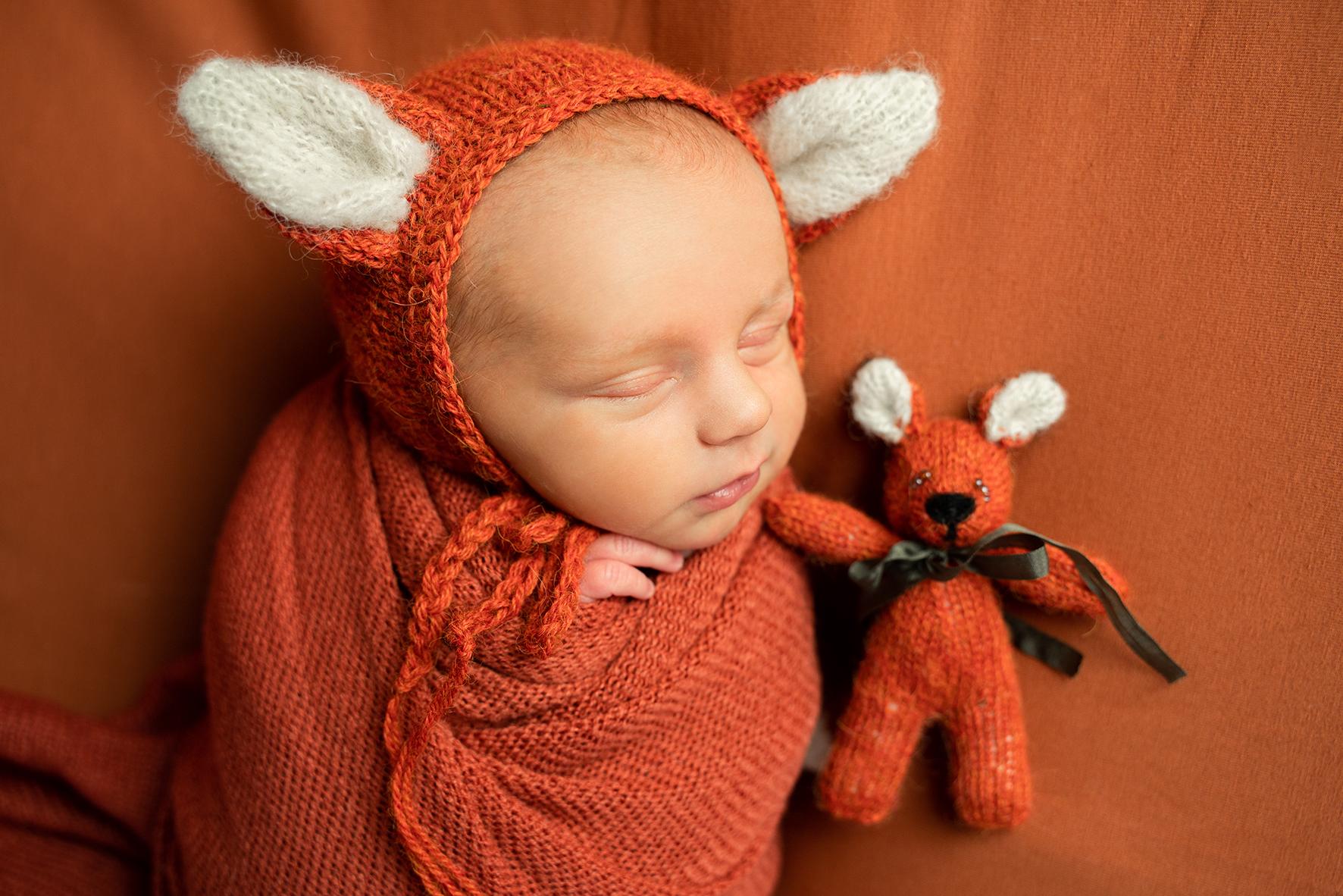 Kleiner Fuchs mit Kuscheltier beim Newbornshooting