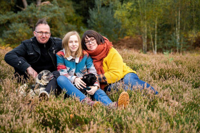 Familienfotos mit Hund in bremen Familienshooting Rotenburg Wümme Familie sitzt gemeinsam mit Haustier in der Heide
