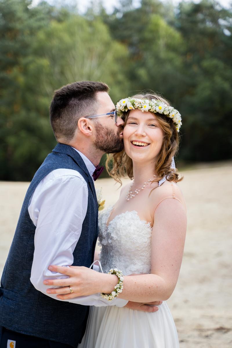 Bräutigam küsst braut auf die Wange Hochzeitsfotograf Syke