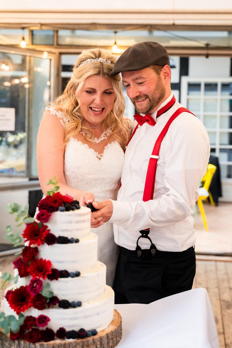 Hochzeitstorte anschneiden bei der Hochzeitsfeier im Landhaus am Deich lachendes Brautpaar Hochzeitsfotos Bremen