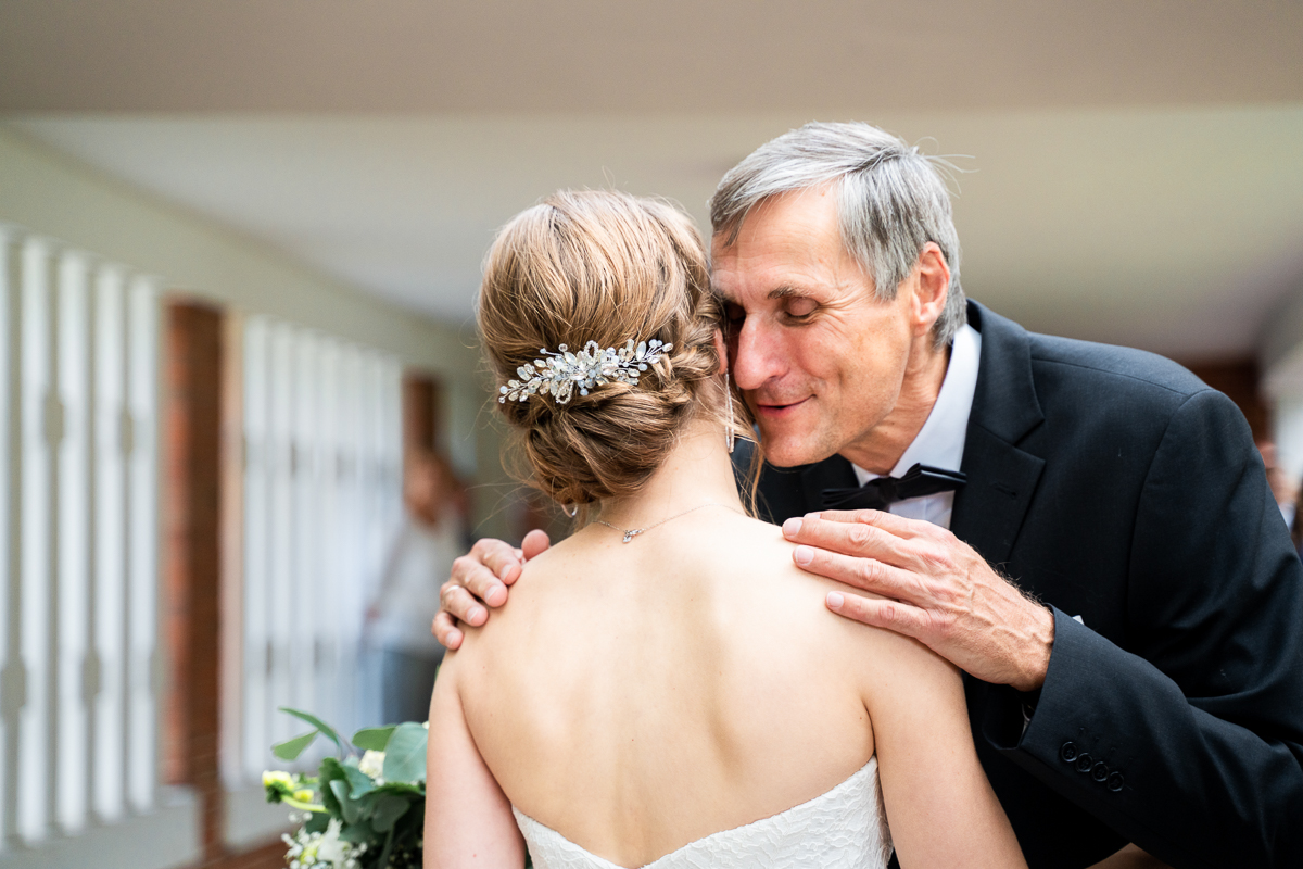 Brautvater umarmt seine Tochter nach der Trauung Hochzeitsfotos Kirchliche Trauung Bremen