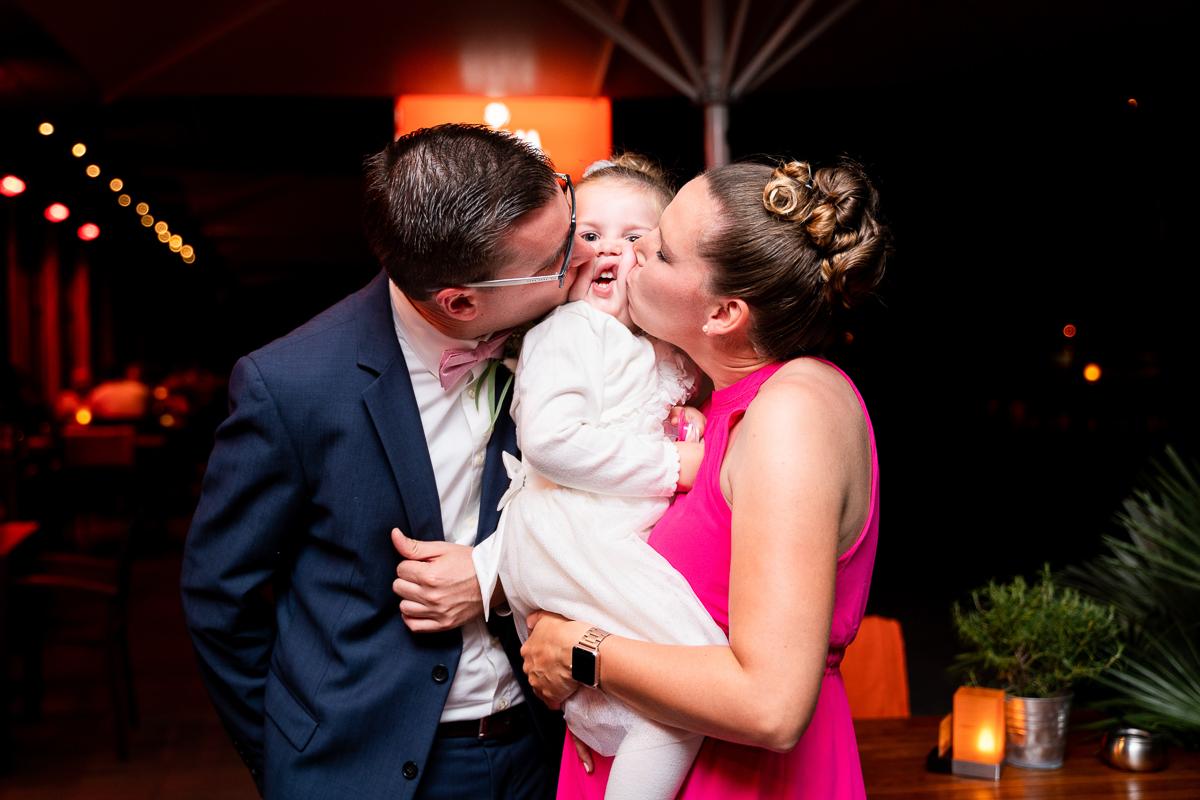 Kind wird von den Eltern geknuddelt Hochzeitsfeier im Riva