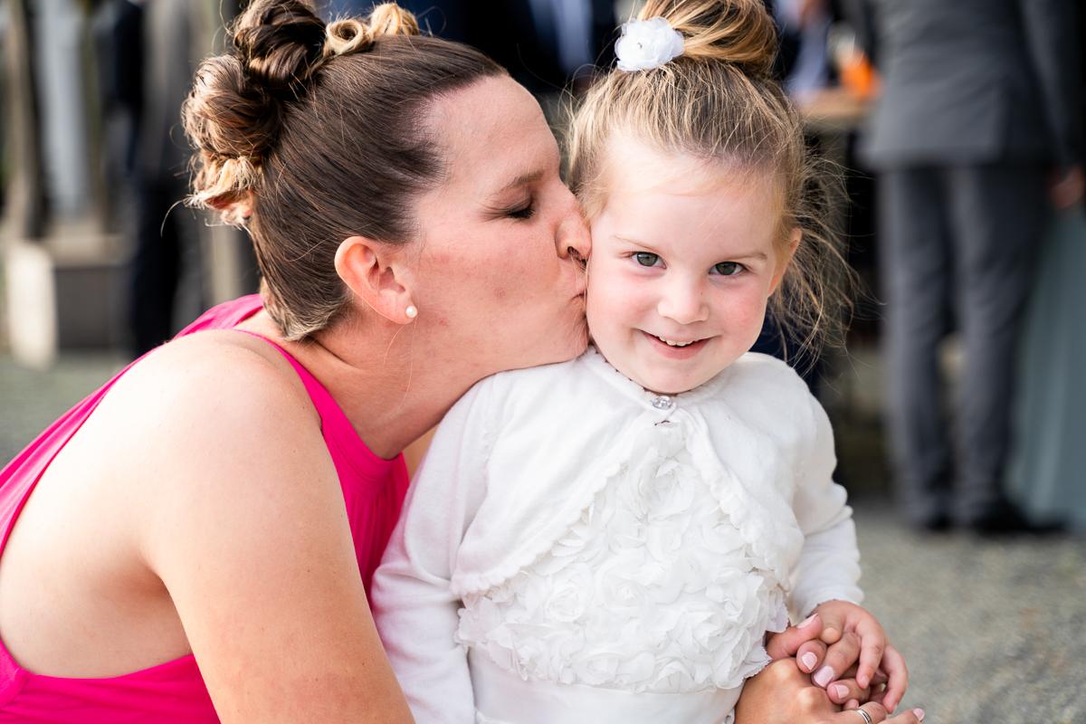 Trauzeugin umarmt Blumenkind bei der Hochzeitsfeier