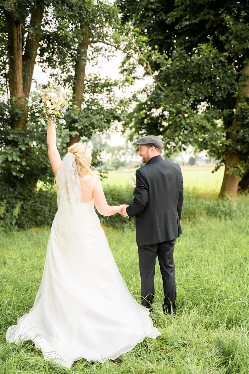 Hochzeitsfotograf Bremen Jubelnde Braut mit Strauß auf der Wiese