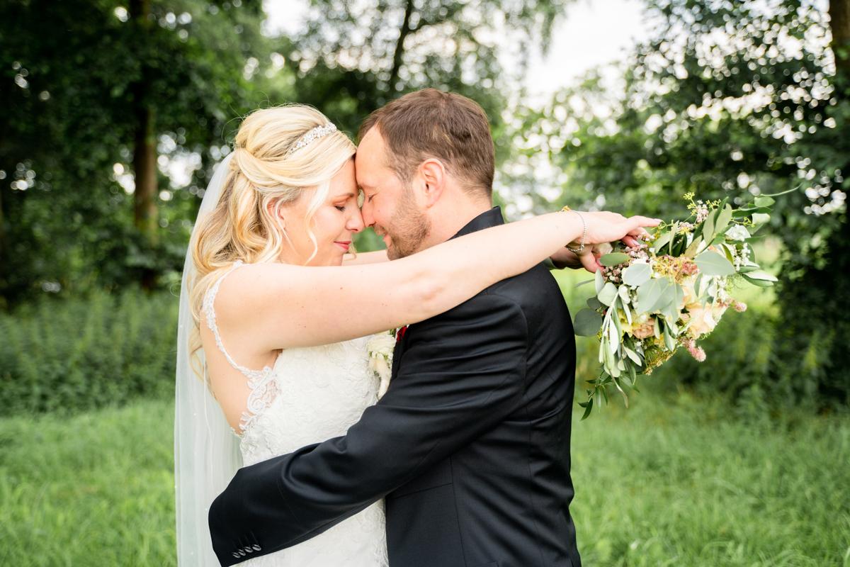 Umarmendes Hochzeitsfoto in Bremen mit Brautstrauß
