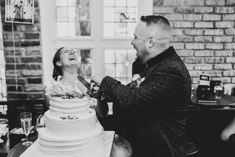 Brautpaar schneidet die Hochzeitstorte an lachende Braut im Hintergrund
