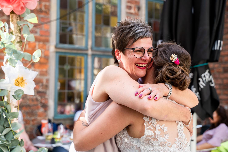 Brautmutter umarmt ihre Tochter herzlich auf der Hochzeitsfeier
