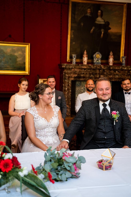 Braut lächelt Bräutigam bei der Trauung im Rathaus an