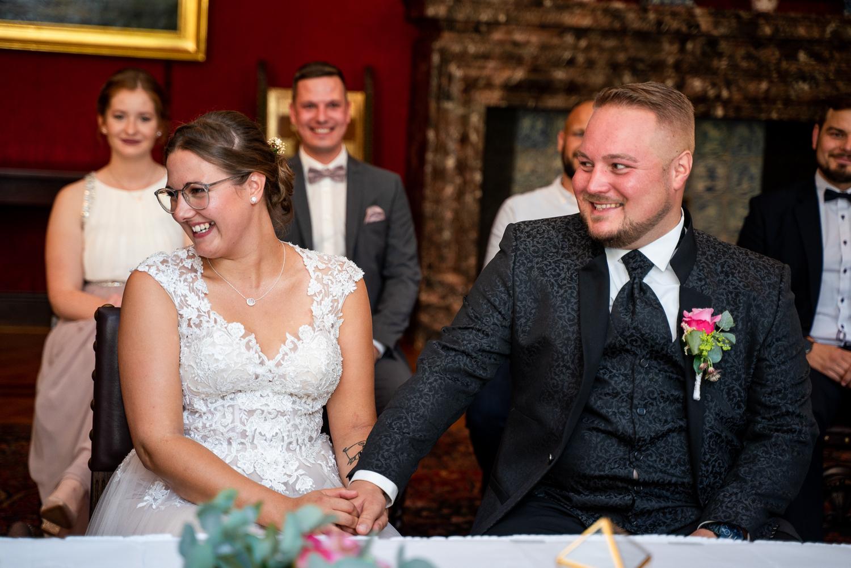 Brautpaar und Gäste lachen herzhaft bei der Trauung im Rathaus Bremen