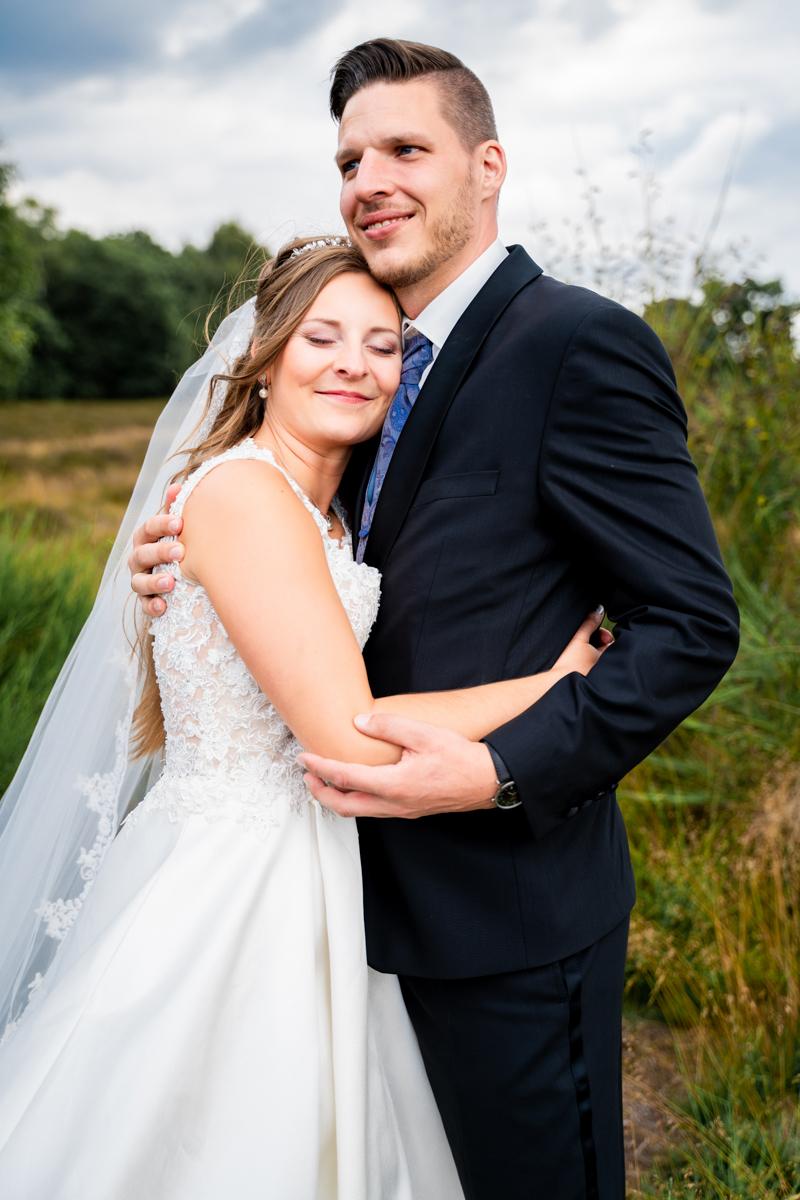 Braut lehnt sich an den Bräutigam Hochzeitsfotos in der Heide