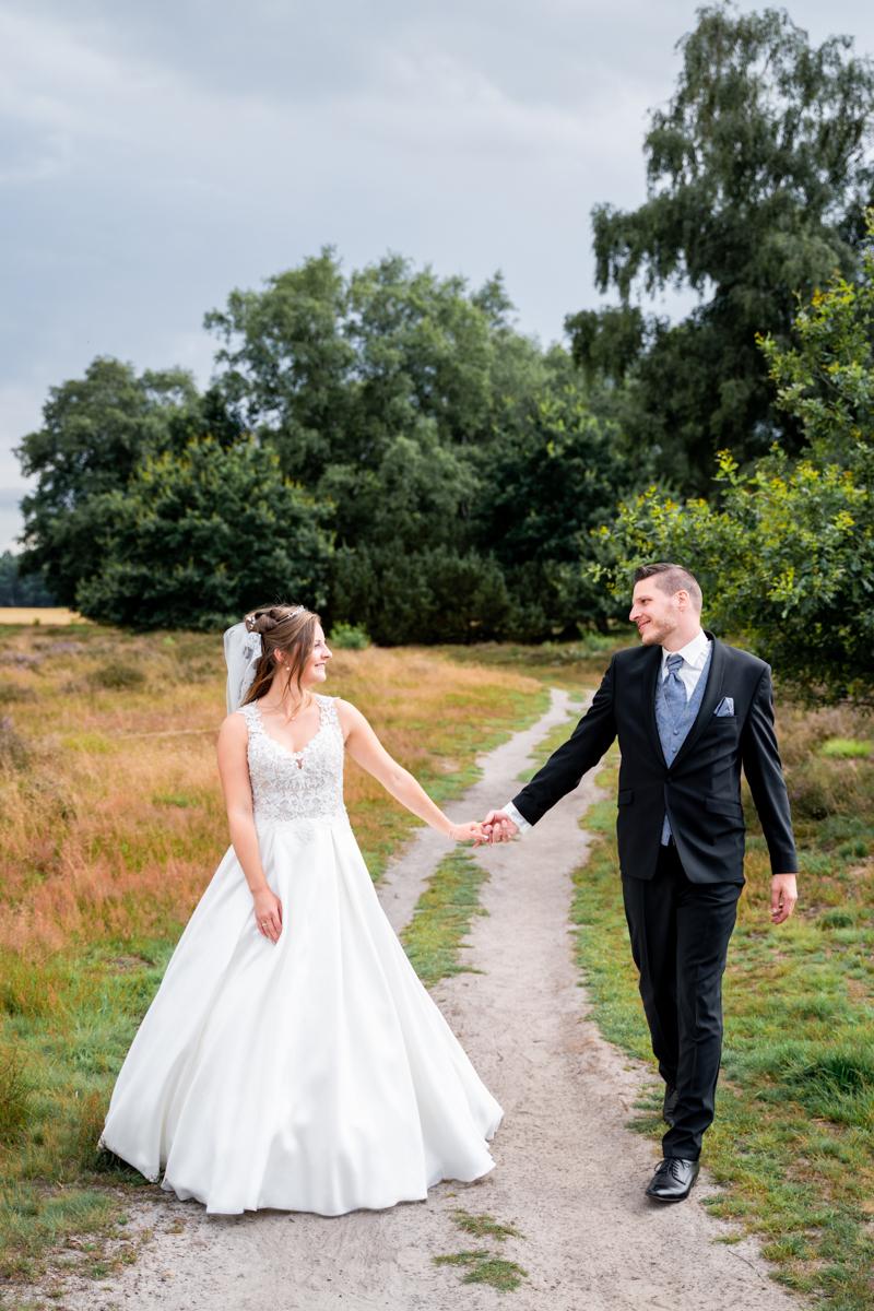 Brautpaar geht durch die Heide spazieren Hochzeitsfotografin Bremen
