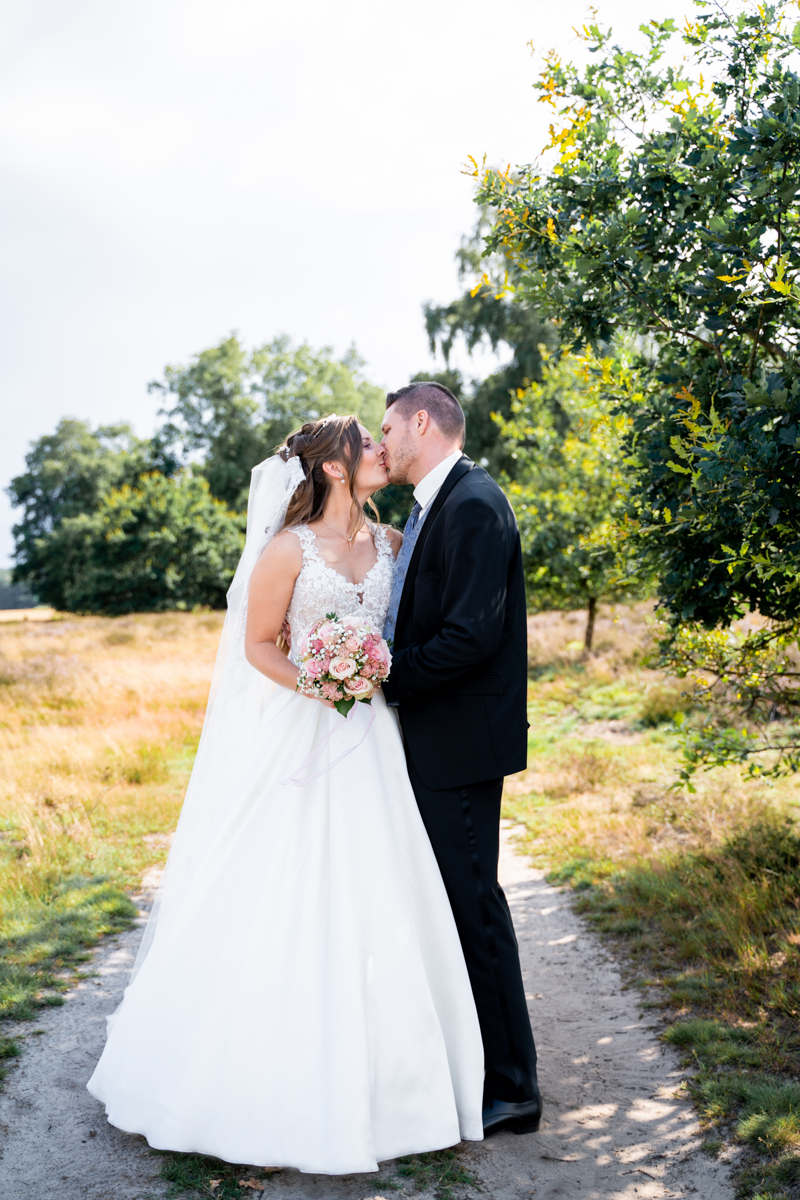 Küssendes Brautpaar auf dem Heideweg Hochzeitsfotografin bremen