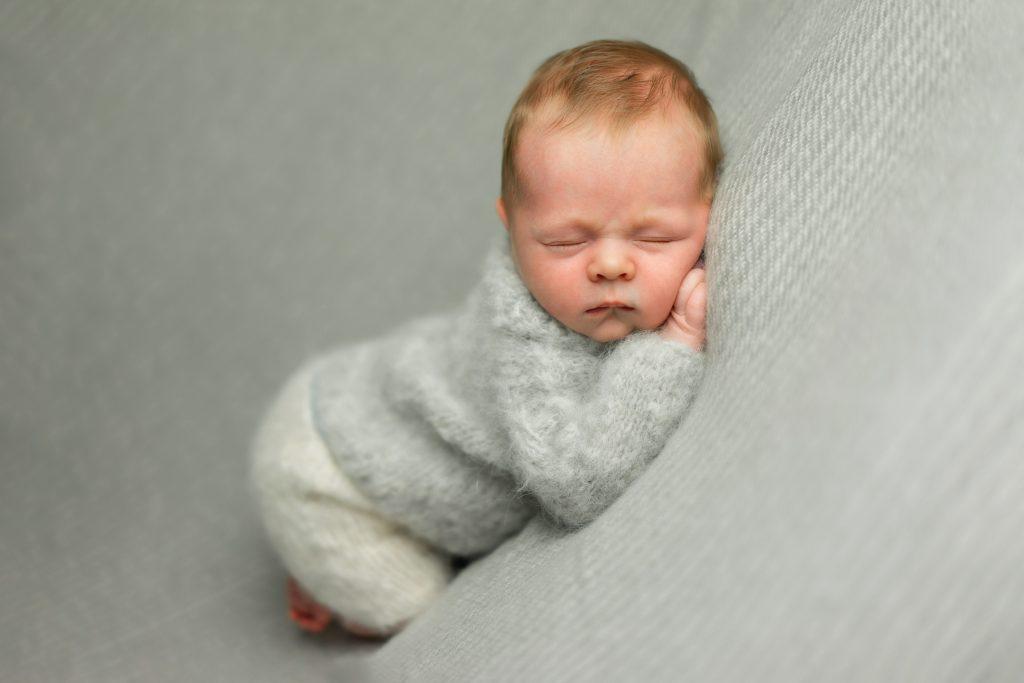 Baby liegt auf dem Bauch im Kuscheloutfit Neugeborenenfotos Bremen