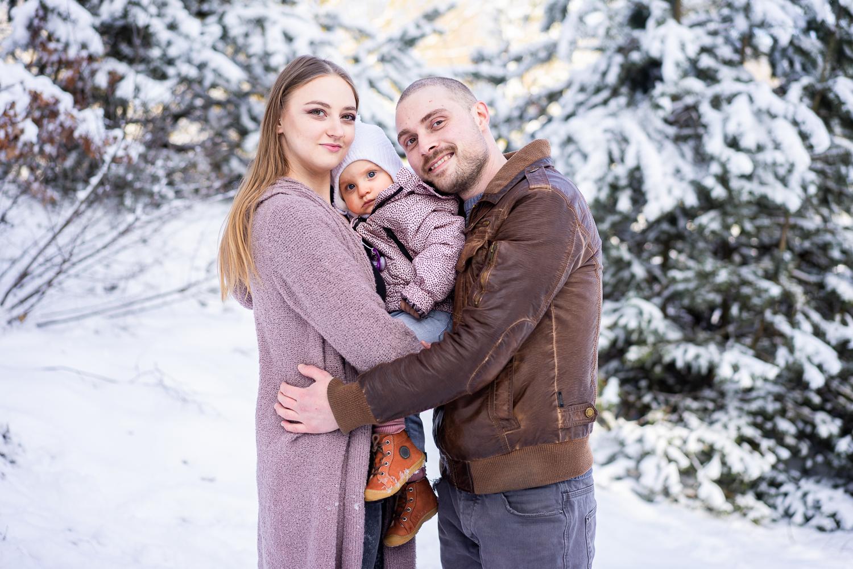 Kuschelnde Familie beim Familienshooting im Schnee