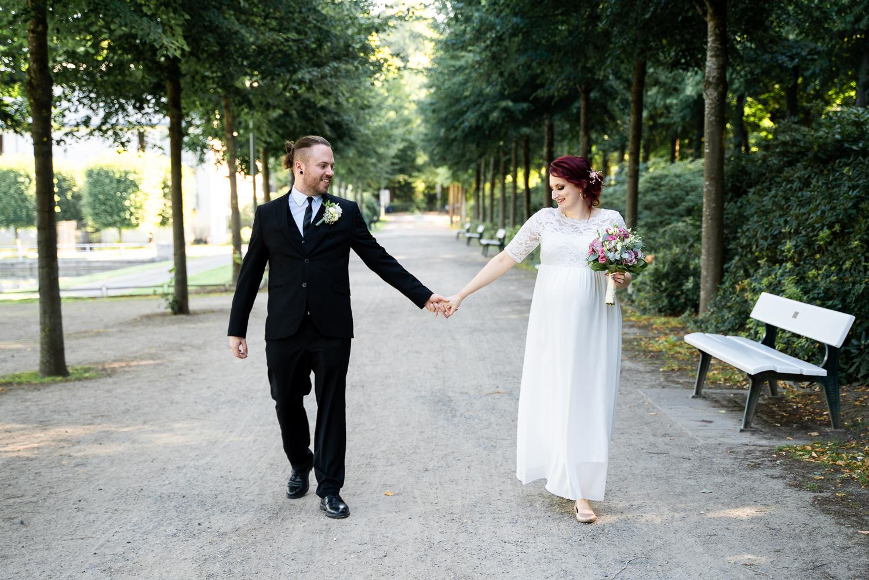 Brautpaar geht gemeinsam durch eine Allee spazieren Hochzeitsfotografin bremen