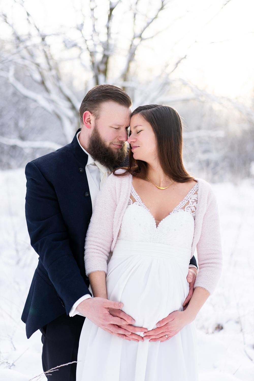 Brautpaar kuschelt gemeinsam im Schnee Babybauchshooting After Wedding Hochzeitsfotos