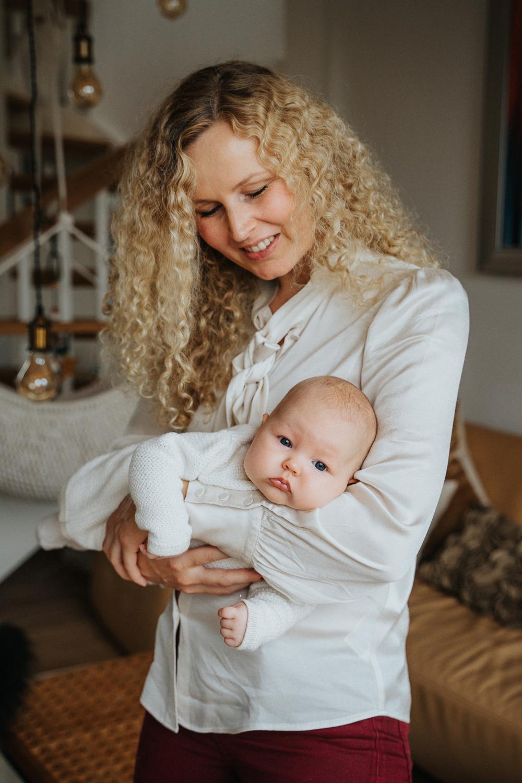 Mama kuschelt mit Baby im Fliegergriff Homestory Familienfotos in bremen