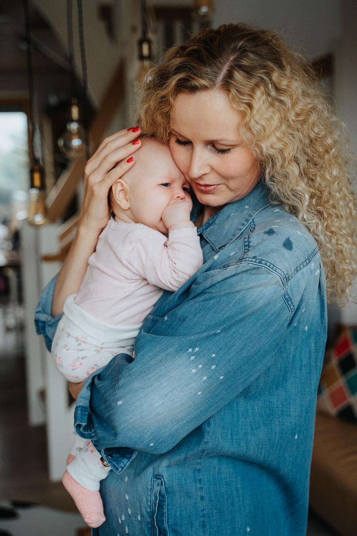 Mama mit Baby kuschelnd Homestory Familienshooting mit Babyfotos Bremen