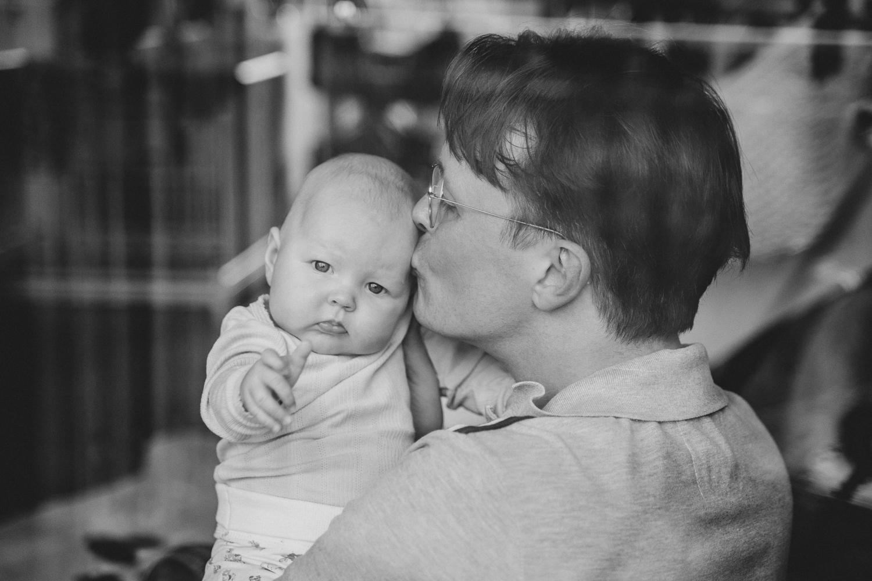 Papa küsst Baby auf die Stirn Familienfotos Zuhause Homestory Neugeborenenfotos
